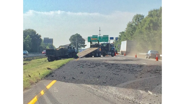 Dump truck overturns on I-64, spilling tar and entrapping an